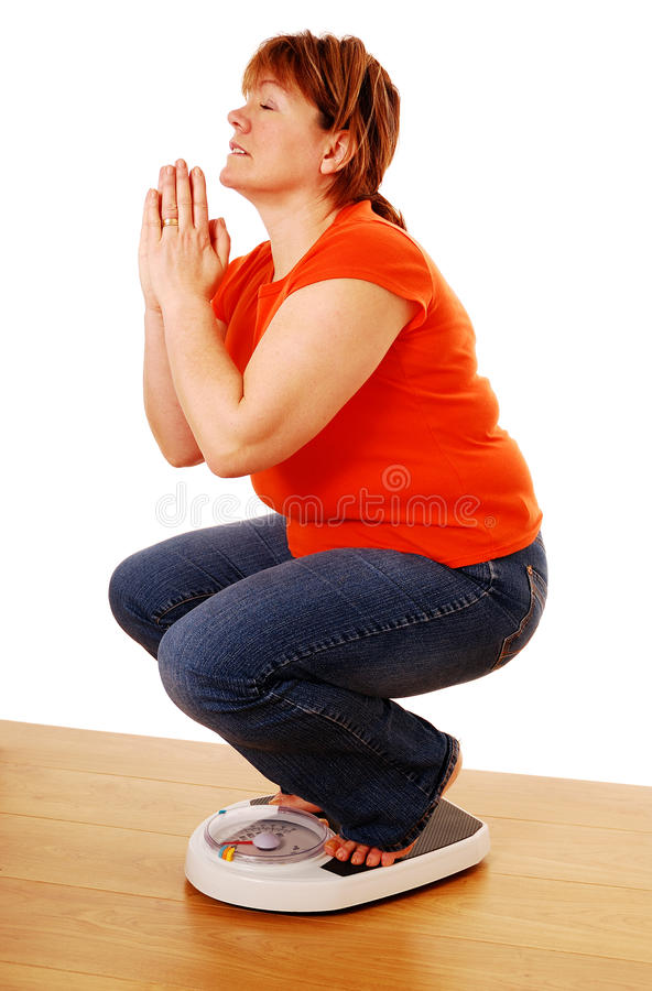 Weight loss. Woman praying for weight loss on bathroom scales stock image
