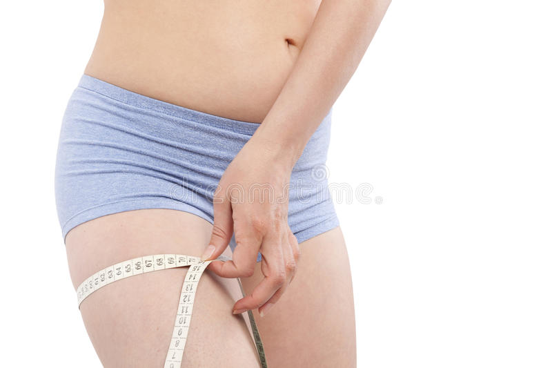 Weight loss. Beautiful caucasian girl in panties measuring her thigh with tape measure isolated on white background. Aesthetic medicine a plastic surgery stock photos