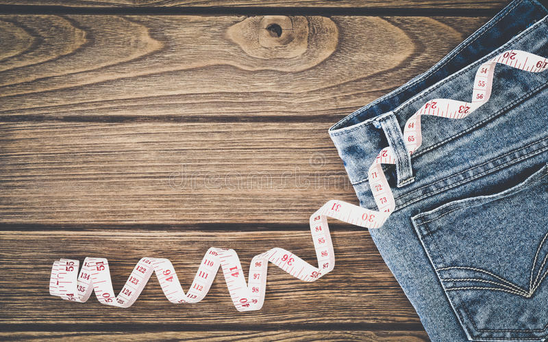 Weight loss concept, Blue jeans and measuring tape on wooden background, Top view with copy space stock images