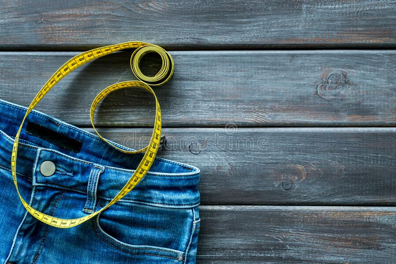 Weight loss concept with jeans and measuring tape on wooden background top view mockup stock image