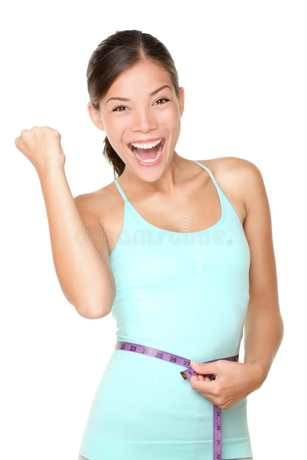 Weight loss concept woman happy. Weight loss concept woman smiling happy excited holding measuring tape around waist. Energetic portrait of sport fitness model royalty free stock photography