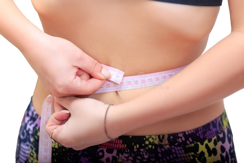 Weight loss, the girl measures the waist. Weight loss, diet result, the girl measures the waist with centimetr, ideal waist 60cm royalty free stock images