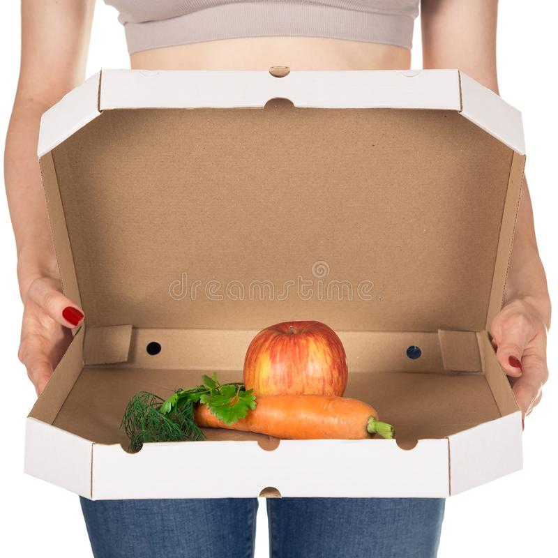 Weight loss and healthy eating or dieting concept. Slim girl with open pizza box and raw vegetables in it. Choice of healthy food instead of junk food. Close stock photo
