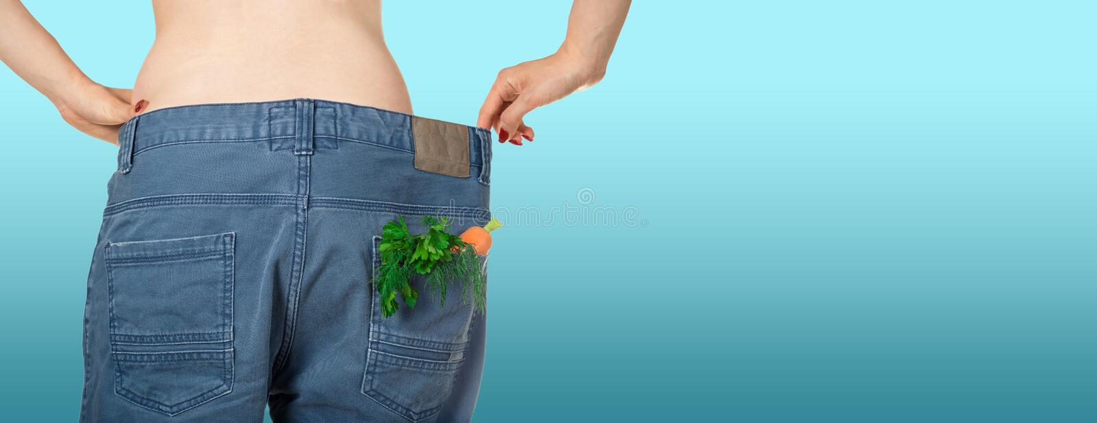 Weight loss and healthy eating or dieting concept. Slim girl in oversized jeans with a carrot, dill and parsley in the pocket. Rear view. Close shot. Mockup stock photo