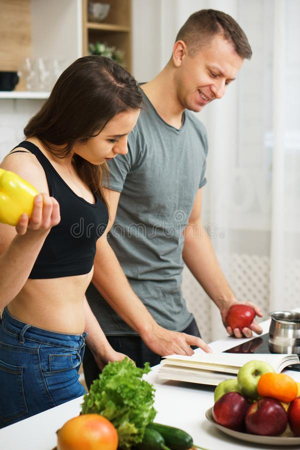 Fit slim couple reading recipe book before cooking. Weight loss, keto, detox, paleo diet food, slimming and healthy lifestyle. fit slim couple reading recipe royalty free stock photos