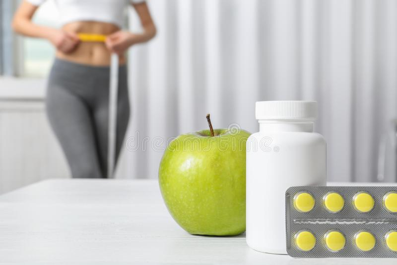 Weight loss pills with apple on table and woman measuring waist indoors. Space for text stock photography