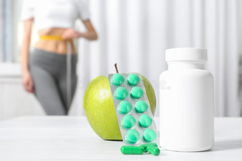 Weight loss pills with apple on table and woman measuring waist. Indoors royalty free stock photo