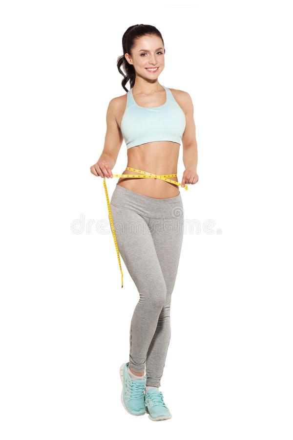 Weight loss, sports girl measuring her waist. Training in the gym, workout abdominals royalty free stock photo