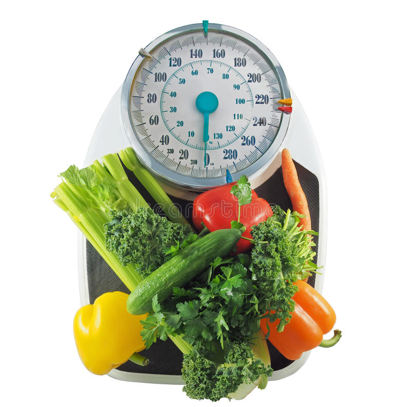 Weight loss. Vegetables on a bathroom scale symbolizing healthy diet for weight loss stock images