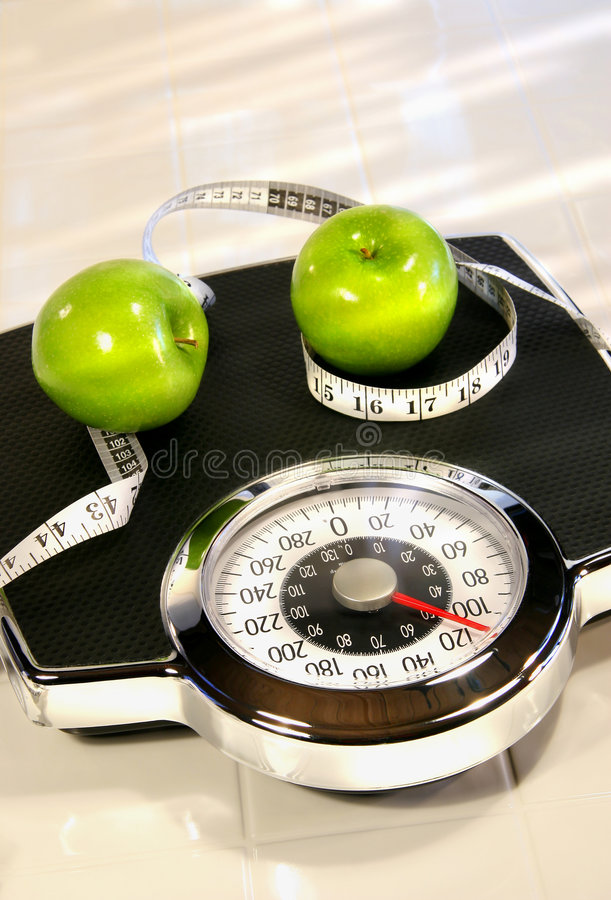 Weight scale with green apples. On white tile floor
