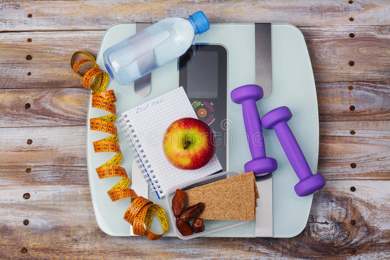 Weight scale, healthy snacks, dumbbells and measuring tape. Healthy eating, diet or weight loss concept royalty free stock photo