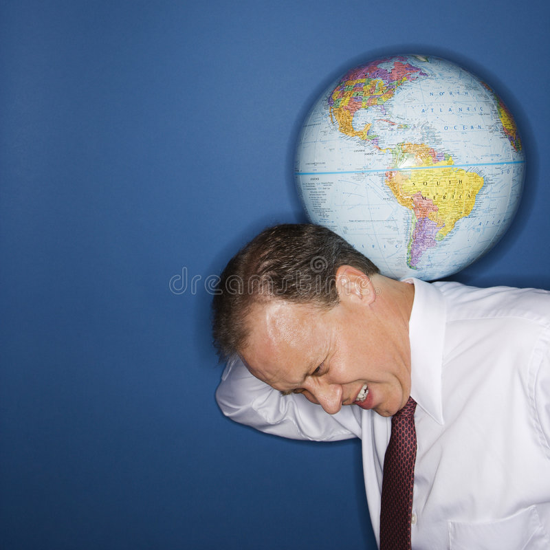 Weight of world. Caucasian middle aged businessman carrying world on shoulders straining stock photo