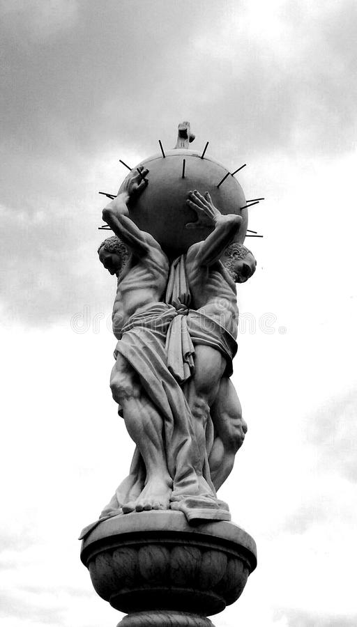 The weight of the world on your shoulders. Statue of two men holding heavy ball stock photo