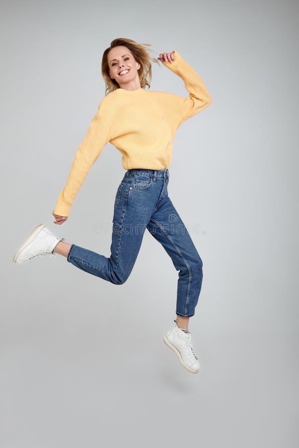 weightlessness De volledige benen, lichaam, grootteportret van mooi verrast meisje met blondehaar kijkt wijd recht in de camera m royalty-vrije stock afbeelding