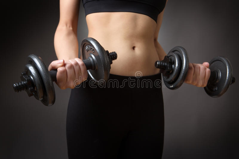 Weightlifting dumbells. Close up shot of a very slim fitness model weightlifting dumbells. low key lighting shot on a grey background royalty free stock photo