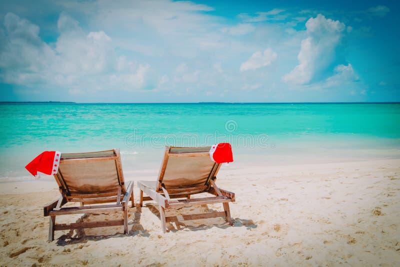 Weihnachten auf Strand - sitzen Sie Aufenthaltsräumen mit Sankt-Hüten in Meer vor lizenzfreies stockbild
