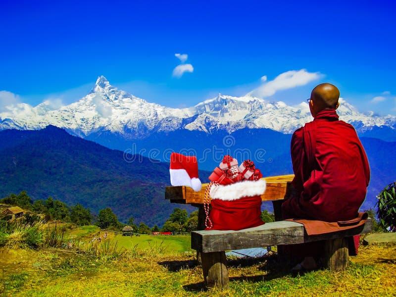 Weihnachten ein buddhistischer Mönch, der voll auf einer Bank mit seinem Weihnachtsmann-Hut und Tasche von Geschenken nahe bei ih lizenzfreie stockfotos