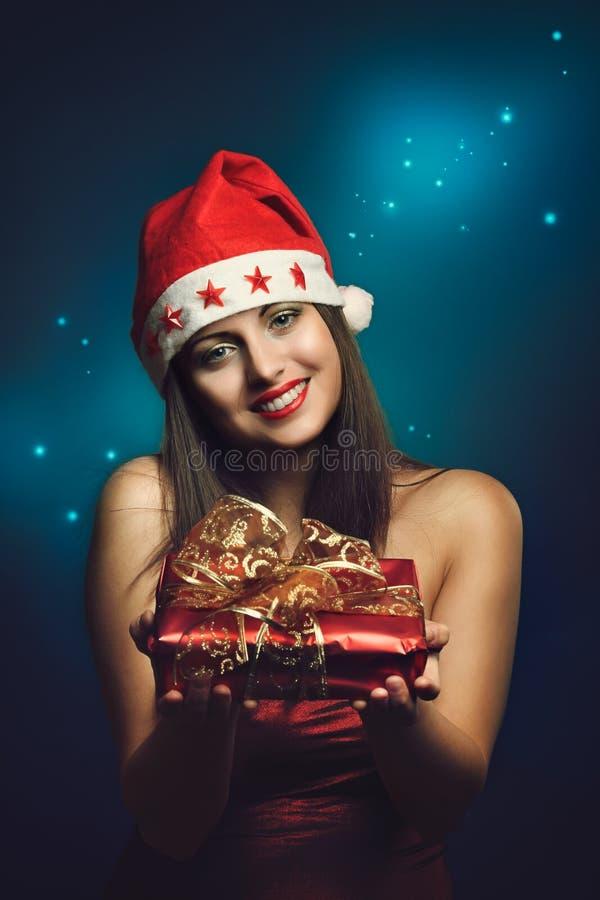 Weihnachten gekleidete Frau, die ein Geschenk anbietet stockfoto