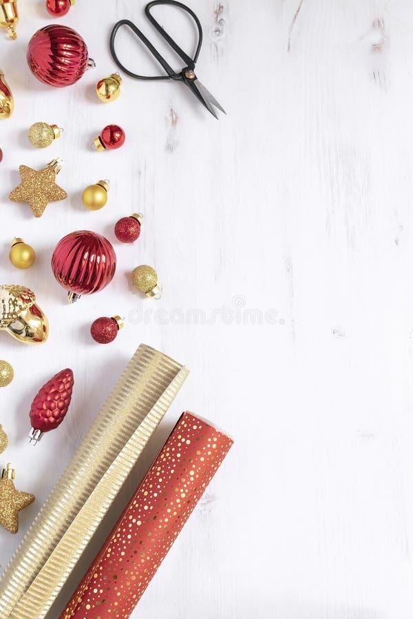 Weihnachten, Hintergrund des neuen Jahres - Packpapier, Scheren und Weihnachts-Rot und Gold-deco Flittergeschenke lizenzfreie stockfotografie