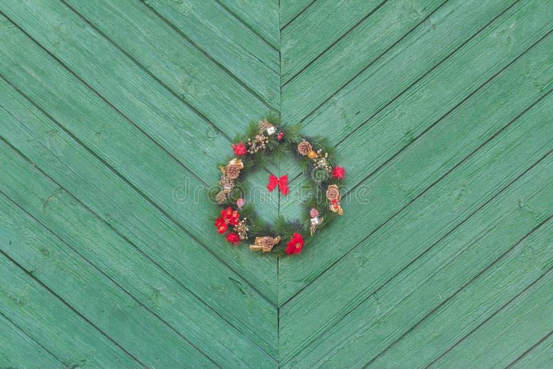 Weihnachten-Holyday-Einführungskranz, der draußen am grünen Holztürhintergrund hängt stockfotos