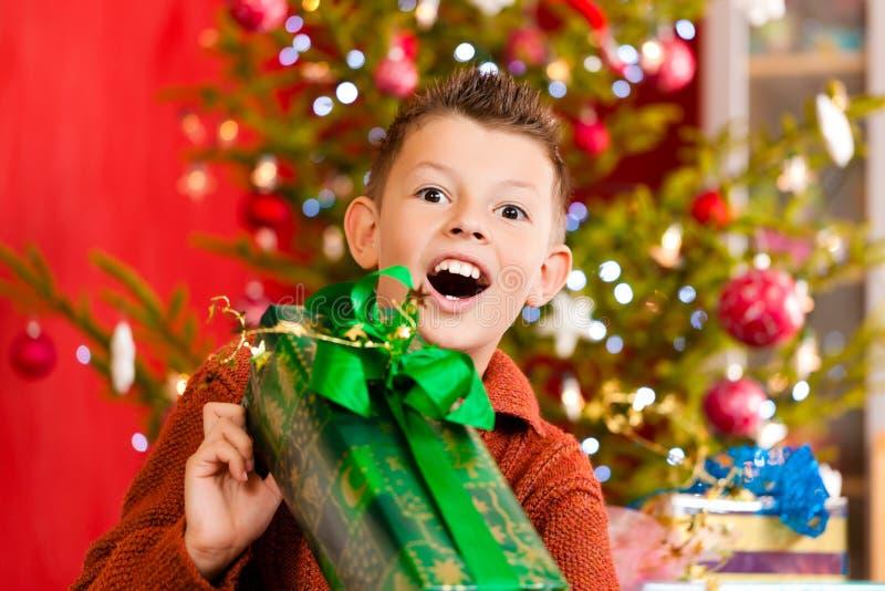 Weihnachten - kleiner Junge mit Weihnachtsgeschenk stockfoto