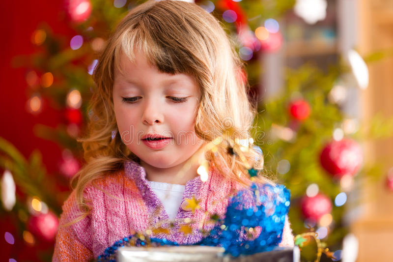 Weihnachten - kleines Mädchen mit Weihnachtsgeschenk stockfoto