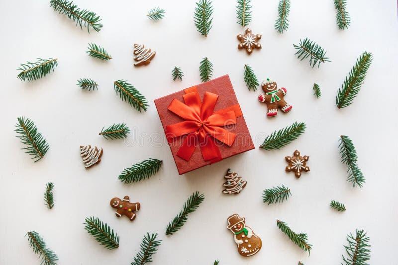 Weihnachten oder Neujahrsgeschenk in einem roten Kasten Sind in der Nähe verschiedene Feiertagssachen einschließlich Ingwerkekse lizenzfreies stockbild