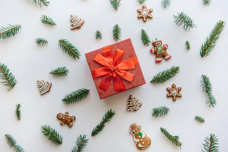 Weihnachten oder Neujahrsgeschenk in einem roten Kasten Sind in der Nähe verschiedene Feiertagssachen einschließlich Ingwerkekse lizenzfreie stockfotos