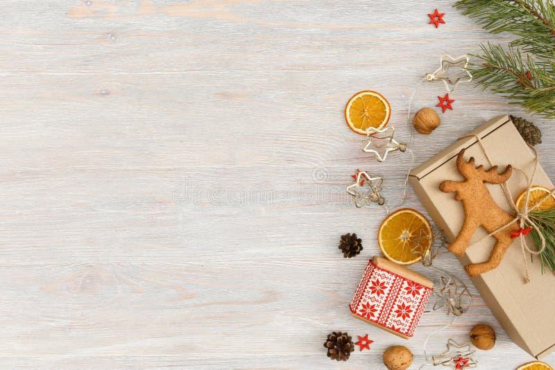 Weihnachten- oder Neujahrshintergrund mit Lebkuchengebäck, Nüssen, Tannenbäumen, Garnelen, getrockneten Orangen, Keulen und stockfoto