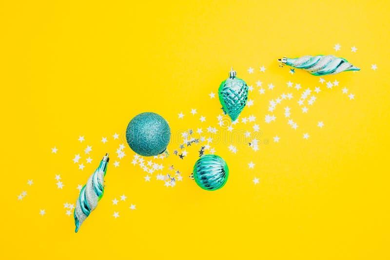 Weihnachten oder Zusammensetzung des neuen Jahres Weihnachtsbälle und silberne Konfettis auf gelbem Hintergrund Flache Lage, Drau lizenzfreie stockfotos