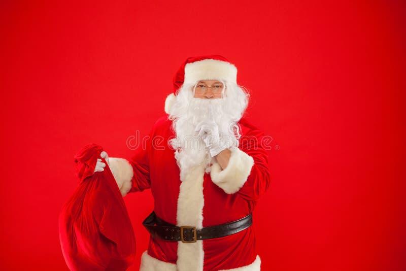 Weihnachten Porträt von Santa Claus mit dem enormen roten Sack, der vorbei Zeigefinger hält stockfotografie