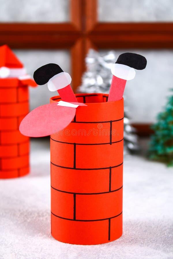 Weihnachten Santa Claus im Kamin machte von der Auflage der Toilettenpapier-Nabe, des farbigen Papiers, der Markierung, des Klebe stockbild
