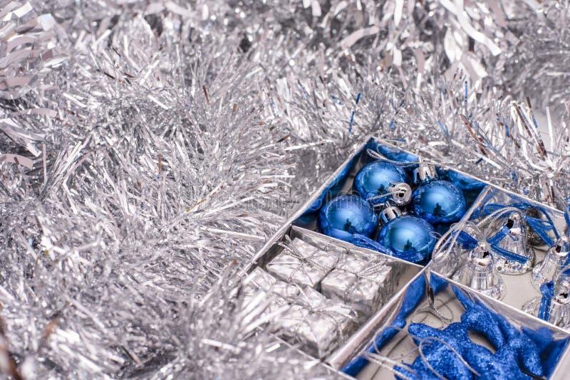 Weihnachten spielt das Bestehen blauen Sternen, blauen Weihnachtsbällen, silbernen Glocken und aus Geschenkboxen im Kasten zwisch stockfotos