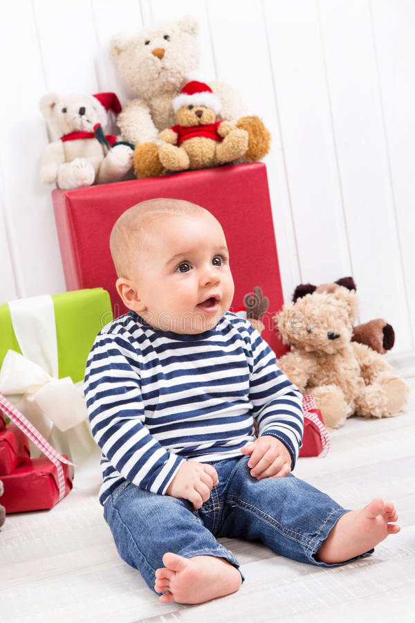 Weihnachten und Geburtstag - nettes barfuß sitzendes und schauendes Baby stockbild
