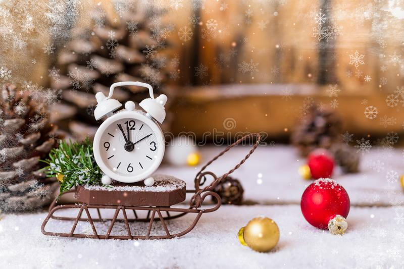 Weihnachten und Wecker des neuen Jahres mit Schnee auf hölzernem Schlitten mit Kegeln und Spielwaren stockfotografie