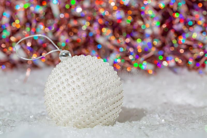 Weihnachten Wei?e Ballperlmuttperlen auf einem Schnee und einem sch?nen unscharfen bunten Hintergrund des funkelnden bokeh mit gl lizenzfreie stockfotos