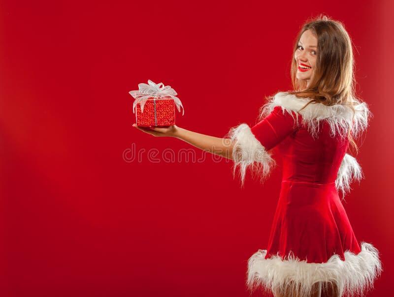 Weihnachten, Weihnachten, Winter, Glückkonzept - lächelnde Frau im Sankt-Helferhut mit Geschenkbox, über rotem Hintergrund lizenzfreies stockfoto