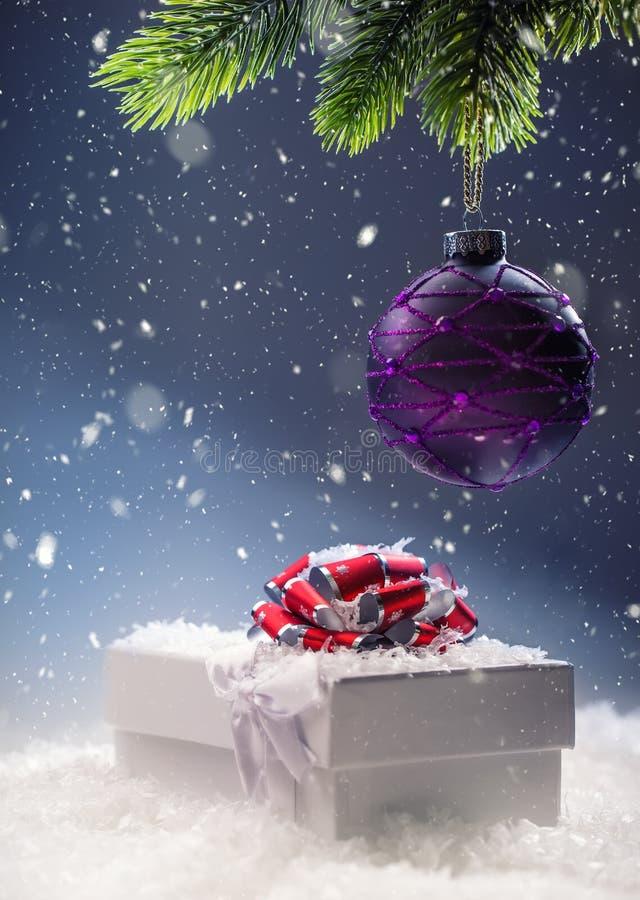 Weihnachten Weihnachtsgeschenkbox in der abstrakten schneebedeckten Szene Rote Hintergrundnahaufnahme stockfoto