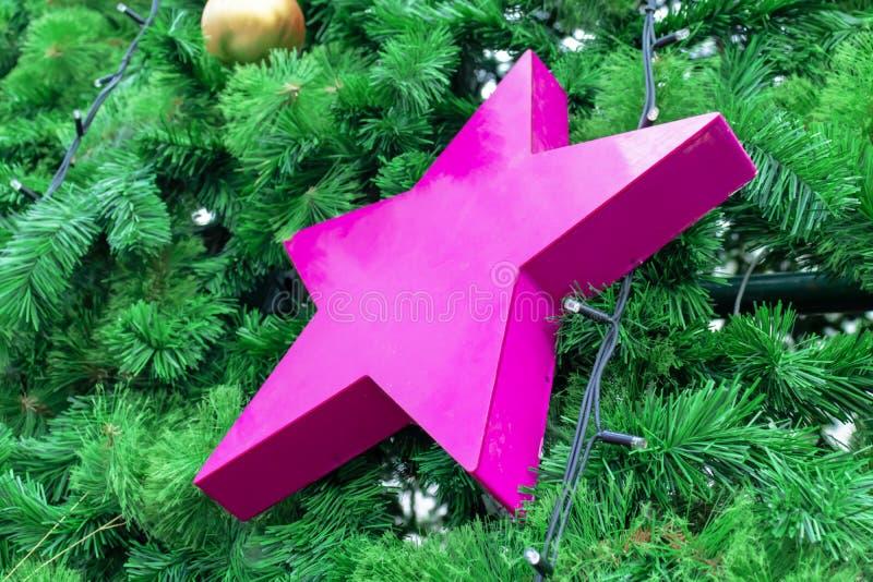 Weihnachts-, des neuen Jahresgrüntannenbaum verziert mit Glaskugeln und großer rosa Stern stockfoto