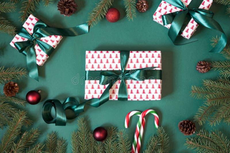 Weihnachts-giftboxes und -geschenke, die im Designpapier und im grünen Band auf Grün mit rotem Dekor einwickeln lizenzfreies stockbild