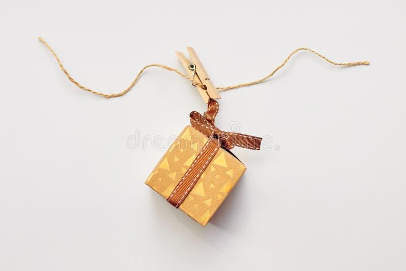 Weihnachts- oder des Feiertagsanwesendes Konzept Handwerkspappgeschenkbox, die am Kleiderhaken über weißem Hintergrund hängt lizenzfreies stockfoto