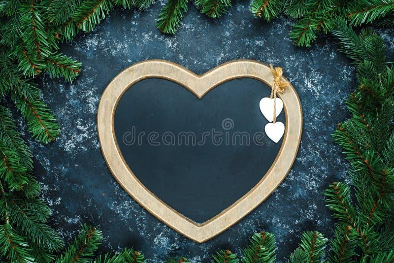 Weihnachts- oder des neuen Jahresdekorationshintergrund: ein Rahmen in Form eines Herzens wird durch Niederlassungen eines Baums  stockfoto