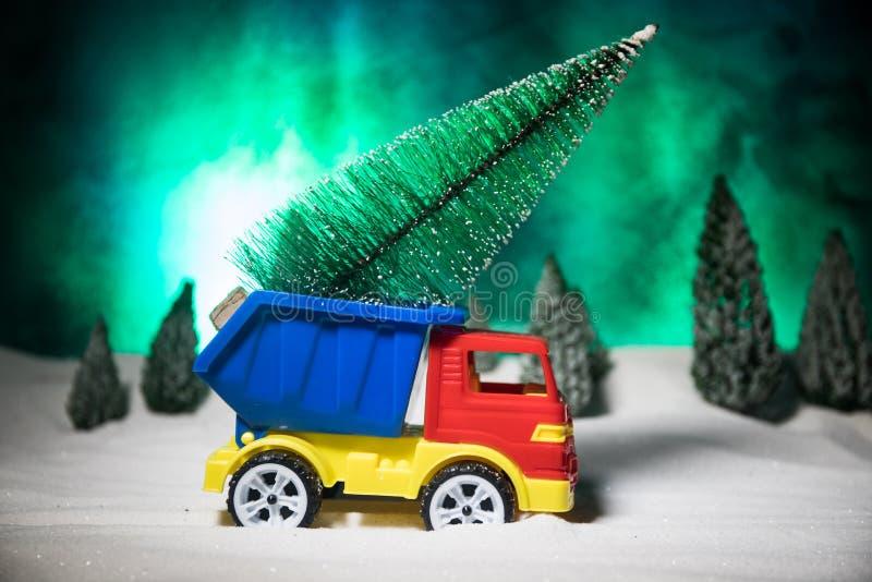 Weihnachts- oder des neuen Jahreskonzept Spielzeugauto, das einen Weihnachtsbaum durch den Wald in den Schneefällen transportiert stockfotos