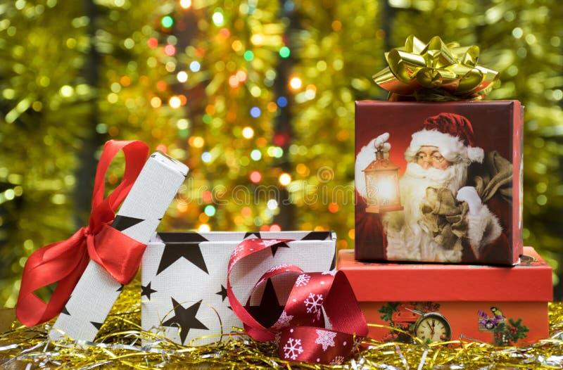 Weihnachts- oder Neujahrsgeschenkkästen und Bänder und goldener leuchtender Hintergrund lizenzfreie stockbilder