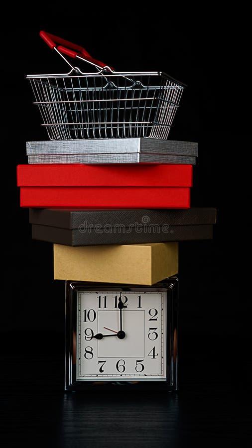 Weihnachts- und Black Friday-Verkaufskonzept mit einem Stapelstapel von Geschenkboxen und von Einkaufskorb auf silberner Uhr auf  stockbilder