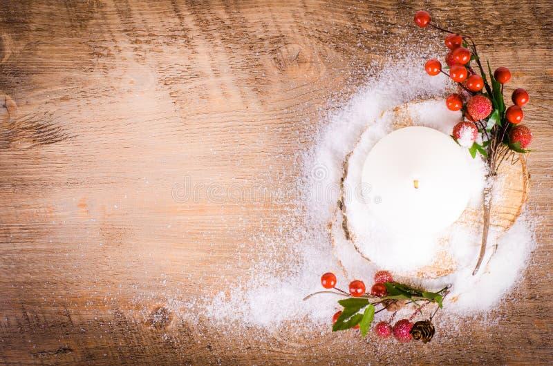 Weihnachts- und des neuen Jahresdekoration - Kerze, Beeren, Schnee, Holz lizenzfreies stockfoto