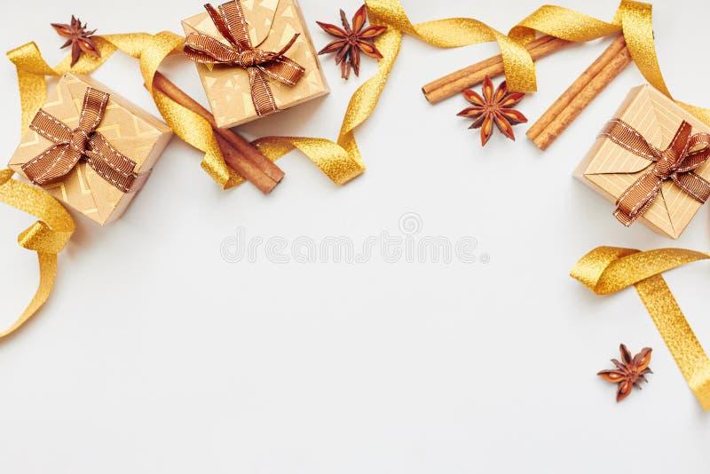 Weihnachts- und des neuen Jahresgrenzzusammensetzung Geschenkboxen mit goldenem Band, Sternanis und Zimt über weißem Hintergrund stockbilder