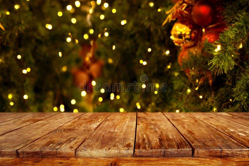 Weihnachts- und des neuen Jahreshintergrund mit leerer dunkler hölzerner Plattformtabelle über Weihnachtsbaum und unscharfem hell stockbilder