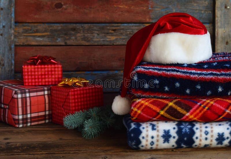Weihnachts- und des neuen Jahreszusammensetzung Plaid, Santa Claus-Hut, Geschenke, Weihnachtsbaumdekorationen auf hölzernem Hint lizenzfreie stockfotografie