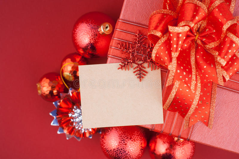 Weihnachts- und guten Rutsch ins Neue Jahr-Geschenkbox mit Dekorationen und Farbball lokalisiert auf rotem Hintergrund stockfotos